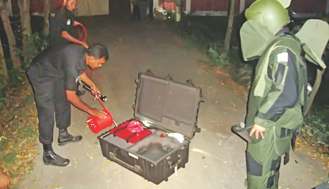Experts defuse a bomb found near the court building of Brahmanbaria in the wee hours of yesterday. Following a tip off, Rab personnel raided the court building and found the bomb near an electricity pole late on Tuesday.  Photo: Focus Bangla