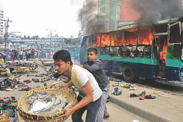 REMINDER FOR PEOPLE A bus burns at Farmgate in the capital yesterday afternoon reminding people that the opposition has called for a two-day hartal from today. Two hawkers who sell shoes are seen trying to gather their merchandise after the arsonists scattered the shoes near the bus. The pre-hartal violence in the capital yesterday saw at least 18 vehicles torched and around 60 others vandalised.  Photo: Star