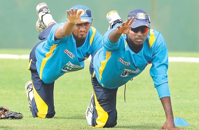 New Sri Lanka captain Angelo Mathews (R) and Suranga Lakmal stretch during a practice session at the Galle International Cricket Stadium yesterday, two days ahead of the first Test against Bangladesh. Photo: AFP