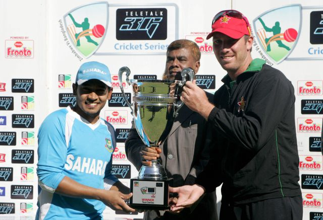 (left) Bangladesh captain Mushfiqur Rahim (L) presents a big smile while sharing the Teletalk Test series trophy with his Zimbabwe counterpart Brendan Taylor after the second Test that the Tigers won by 143 runs at the Harare Sports Club ground yesterday.  Photos: AFP