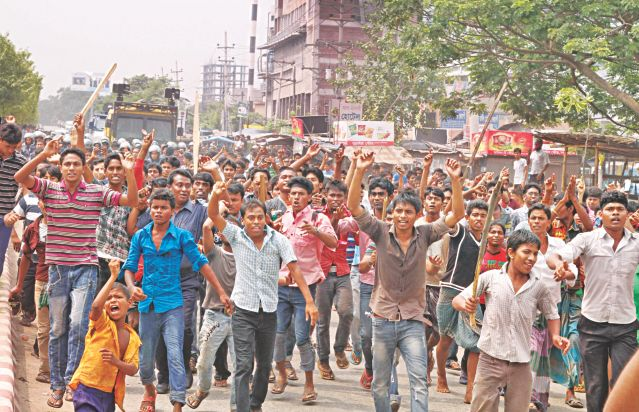 Garment workers demonstrate with sticks in their hands at Genda in Savar area on the outskirts of the capital yesterday demanding trial of those responsible for the death of labourers in Rana Plaza building collapse in the area on Wednesday. Photo: Star