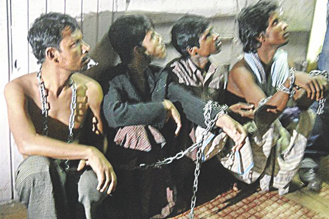 Four Myanmarese are seen chained together in a room. Malaysian police rescued them along with 11 Bangladeshis on Thursday. They had apparently fallen victim to an illegal immigrant-trafficking syndicate. Photo: The Star (Malaysia)