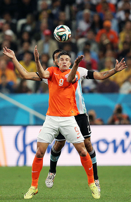 Robin van Persie of the Netherlands and Ezequiel Garay of Argentina compete for the ball clash during their semi-final match at The Corinthians Arena in Sao Paulo on July 9, 2014. Photo: Getty Images