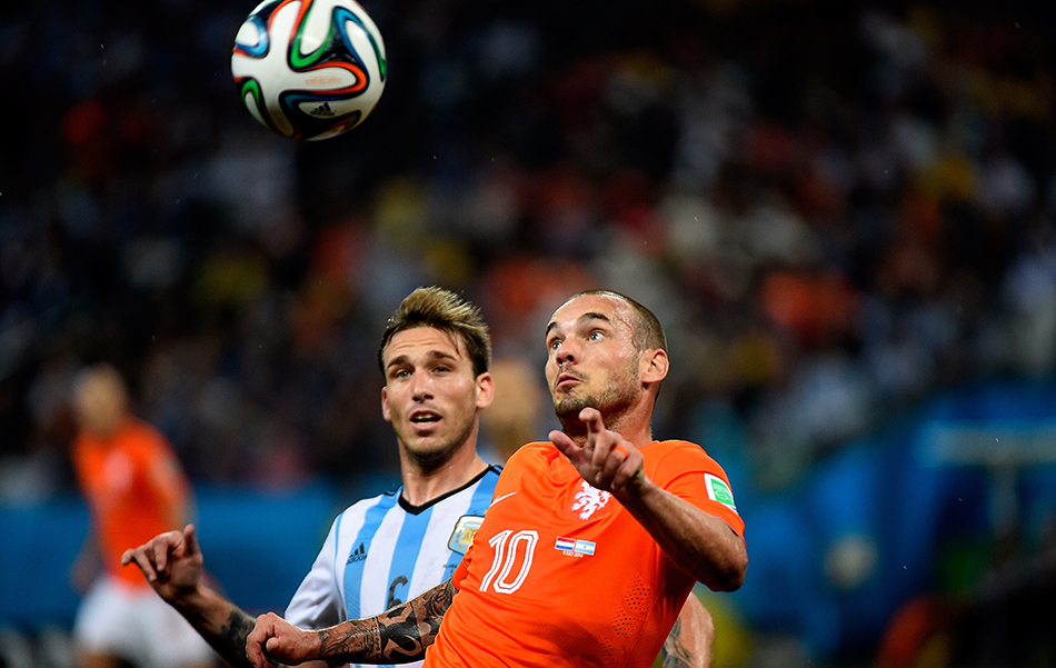 Netherlands' midfielder Wesley Sneijder (R) and Argentina's midfielder Lucas Biglia challenge for the ball during their semi-final match at The Corinthians Arena in Sao Paulo on July 9, 2014. Photo: Getty Images