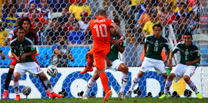 Netherlands' Wesley Sneijder shoots and scores his team's first goal past Guillermo Ochoa of Mexico during their World Cup Round of 16 match at Castelao on June 29, 2014 in Fortaleza, Brazil. Photo: Getty Images
