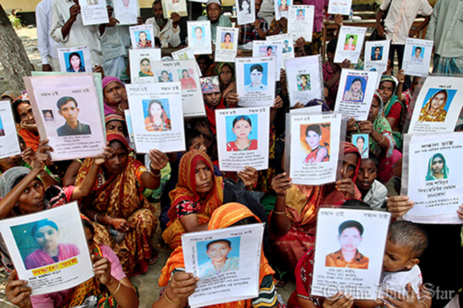 Relatives hold up photos of missing workers. Photo: Star