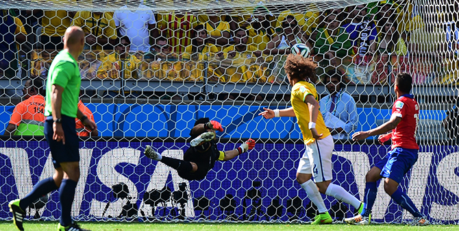 Chile's goalkeeper and captain Claudio Bravo (C-L) fails to save a goal by Brazil's defender David Luiz (C-R) during the Round of 16 football match between Brazil and Chile at The Mineirao Stadium in Belo Horizonte during the 2014 FIFA World Cup on June 28, 2014. Photo: Getty Images