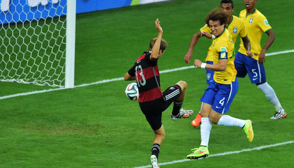 Germany's forward Thomas Mueller (L) scores his team's first goal during the semi-final football match between Brazil and Germany at The Mineirao Stadium in Belo Horizonte during the 2014 FIFA World Cup on July 8, 2014. Photo: Getty Images