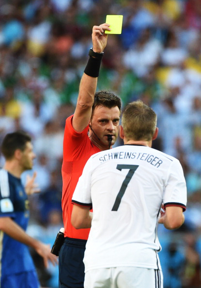 Italian referee Nicola Rizzoli (L) shows a yellow card to Germany's midfielder Bastian Schweinsteiger (R) during their 2014 FIFA World Cup final match at the Maracana Stadium in Rio de Janeiro on July 13, 2014. Photo: Getty Images