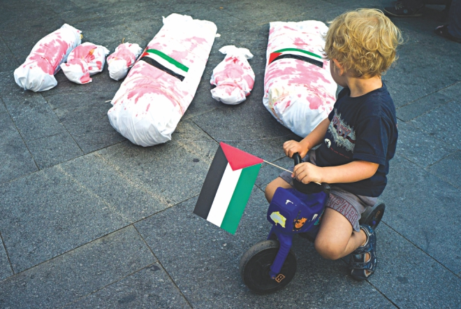 A boy holding the Palestinian flag rides on his plastic motorbike around mock-ups of dead Gaza residents during a rally in solidarity with Palestinians in Prague. Photo: AFP