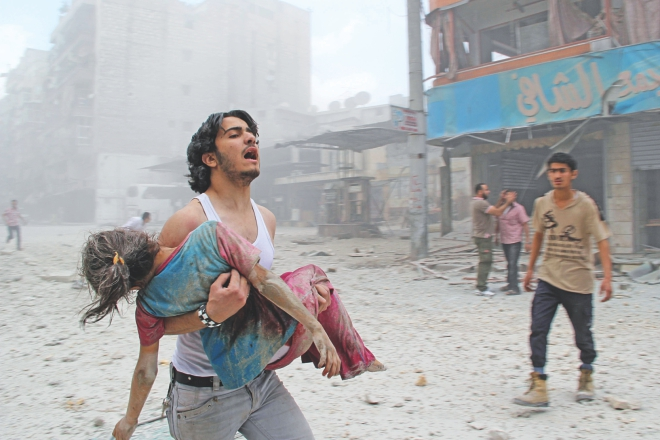 A man carries a young girl who was injured in a reported barrel-bomb attack by government forces in Aleppo, yesterday.  Photo: AFP
