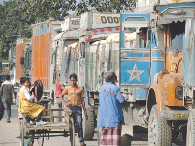 A man (marked X), engaged by the leader of a so-called labourers' association, demands illegal toll from an Indian truck driver at Burimari land port a couple of days ago.   PHOTO: STAR