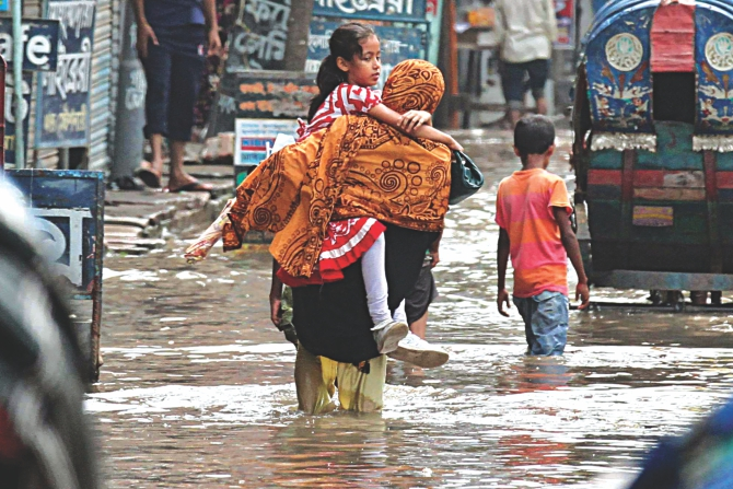 A mother picks up her school-going child in her arms to take her to school through knee-deep water on Ziaur Rahman Sarani in Matuail. Photo: Anisur Rahman