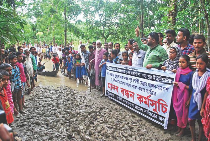 People of Raipasha-Karapur union in Barisal Sadar upazila formed a human chain at Dharmadi-Raipasha point of a two-kilometre-long muddy road on Sunday, demanding that the authorities concerned convert the road near the city into a metalled one. Photo: Star