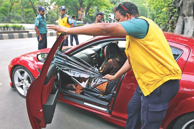 A policeman tears off the tinted sheet from the window of a sports car on Minto Road in the capital yesterday after the deadline for motorists to remove the tinted windows and screens from their vehicles ended on Saturday.  Photo: Amran Hossain