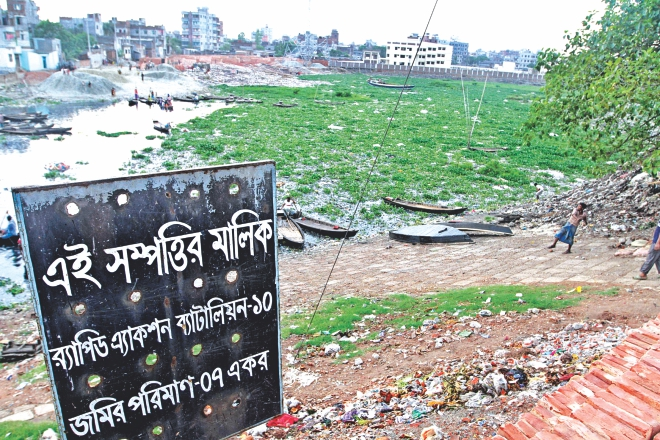 "A sign at Sharifnagar of Kamrangirchar in the capital claiming that the seven acre ""land"" belongs to Rab-10, which in reality is a channel of the Buriganga. The government yesterday finally cancelled the allocation. Photo: Amran Hossain"