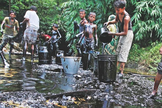 A train carrying furnace oil derails in Foujdarhat, Sitakunda in Chittagong spilling oil into a canal nearby. Locals scoop up the oil in their buckets to get some money by selling it. Photo: Anurup Kanti Das