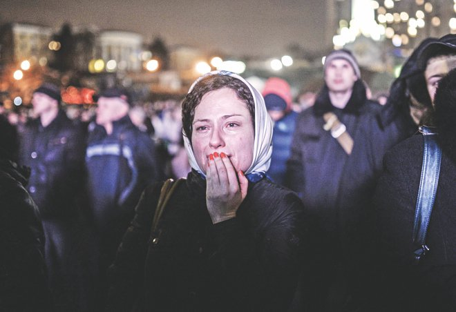 A woman cries as she stays on Kiev's Independence Square, yesterday. Photo: AFP