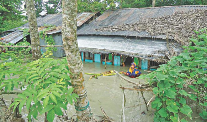 A woman stands in waist-deep water in front of her house at flood-hit Naziuddin village in Charfasion upazila of Bhola district. Photo: Star