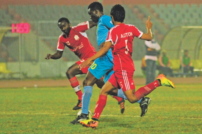 Abahani's Awudu Ibrahim (C) is sandwiched in between two defenders of Feni Soccer Club during their Bangladesh Premier League match at the Bangabandhu National Stadium yesterday. PHOTO: STAR
