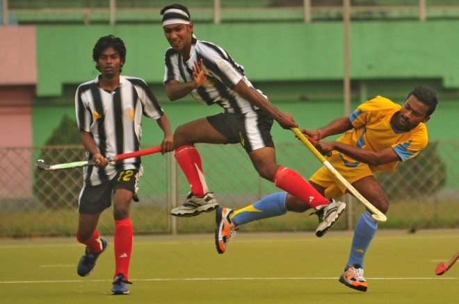 Abahani's Jubair Hasan Niloy (R), who is executing a reverse-hit to score his team's fourth goal, sends a Dhaka Wanderers defender (C) running for cover during the opening match of the UCB Club Cup hockey tournament at the Maulana Bhasani National Hockey Stadium on Tuesday. PHOTO: STAR