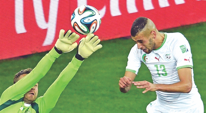 Islam Slimani (R) heads in the equaliser against Russia at Curitiba to fire  Algeria into the last 16 of the World Cup for the very first time.  PHOTO: AFP