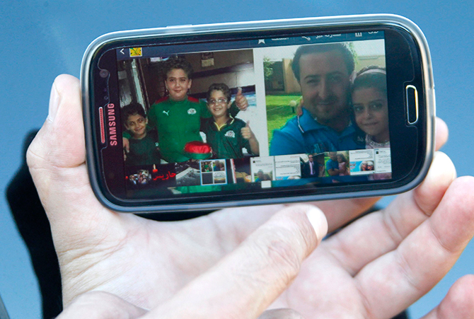 A relative of Lebanese national Manji Hasan holds up his mobile phone displaying a picture of Manji and his children, who the family said were all on board Air Algerie flight AH 5017, in the southern Lebanese village of Hariss July 24, 2014. The Air Algerie flight crashed on Thursday en route from Ouagadougou in Burkina Faso to Algiers with 110 passengers on board. Photo: Reuters