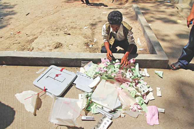 A man rummages through ballot papers and box thrown out of a polling station in Comilla's Brahmanpara during an attack by AL supporters yesterday. Photo: Star