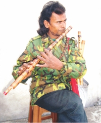 Amir Hamza playing his flute at a market in Jhenidah. PHOTO: STAR