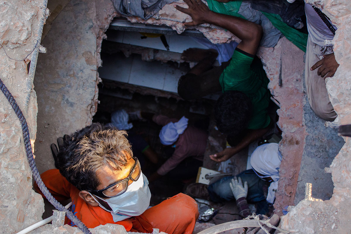Volunteers go down through a dug tunnel in search of survivors. Photo: Anik Rahman