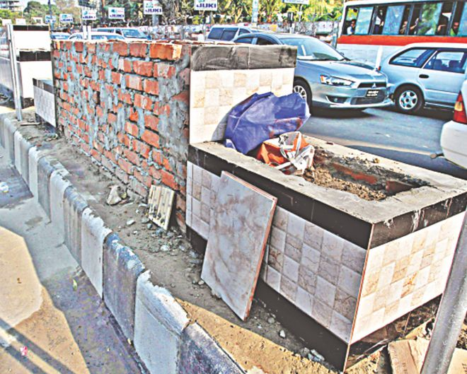 "Brick structures wrapped with kitchen and toilet tiles are being built on the central reservation of a thoroughfare near Mohakhali flyover as part of a ""beautification project"" launched by Dhaka North City Corporation ahead of the ICC T20 World Cup. Photo: Anisur Rahman"