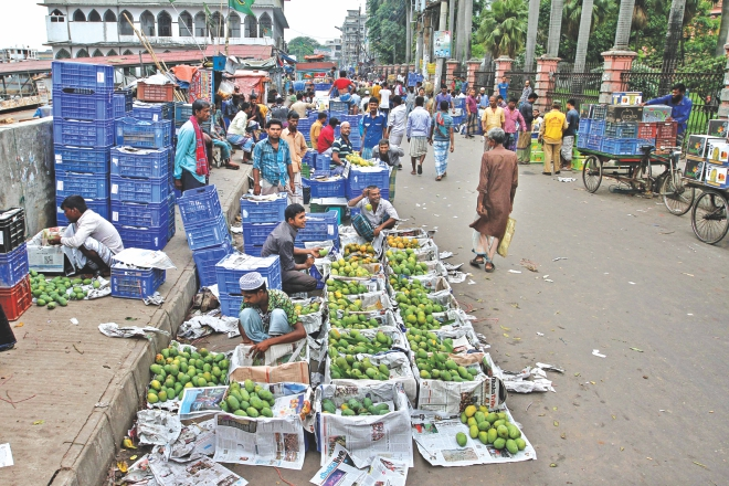 Fruit wholesalers sit in their makeshift shops on Badamtoli Road in Old Dhaka yesterday morning with hardly any buyers. Usually, the street is teeming with buyers in the mornings. Photo: Anisur Rahman