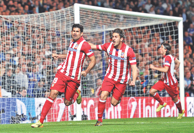 Atletico Madrid forward Diego Costa (L) celebrates with teammate Koke (C) after scoring his team's second goal from a penalty during their 3-1 win over Chelsea in the Champions League semifinal second leg match at Stamford Bridge in London yesterday. PHOTO: AFP