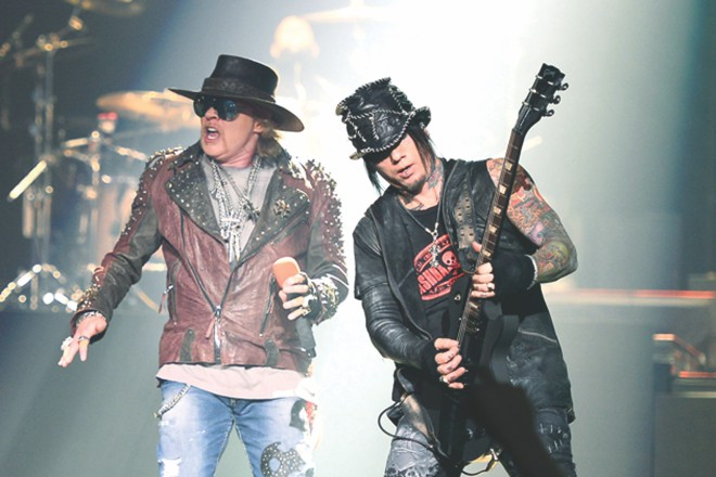 Axl Rose and DJ Ashba live on stage.