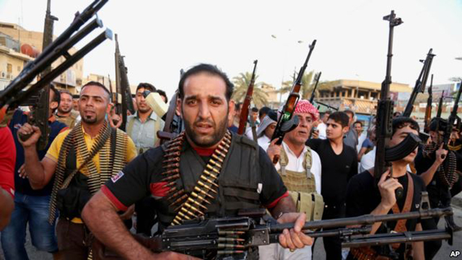Iraqi Shia tribal fighters deploy with their weapons while chanting slogans against the al-Qaeda-inspired Islamic State of Iraq and the Levant, in Baghdad's Sadr City, Iraq, June 13.