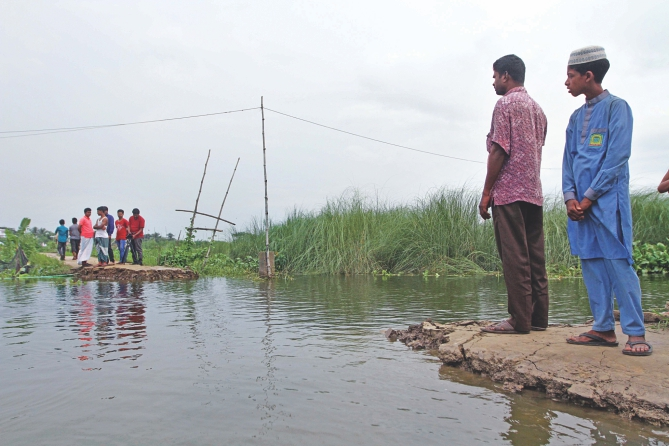 A 25-foot stretch of a road was swept away by water from the swelling Balu River in Kazir Jaiga village of the capital's Khilgaon Monday. With the road broken, over a hundred students from Nagdarpur and Nasirabad villages now have to make a 1.5km detour or use boats to go to Prof Ali Ahmad School and College in Kazir Jaiga. The sudden onrush has also adversely affected fish farming in a large swathe of the low-lying area. The photo was taken yesterday. Photo: Palash Khan
