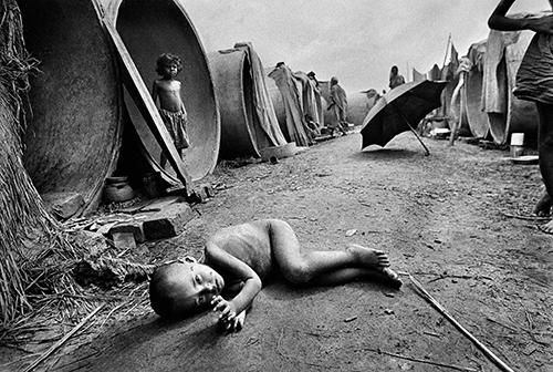 A malnourished refugee child from Bangladesh lies on the ground at a shabby camp in India. Raghu Rai/Magnum Photos