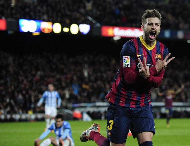 Barcelona defender Gerard Pique celebrates his opening goal against Malaga during their Primera Liga encounter at Nou Camp on Sunday. Photo: AFP