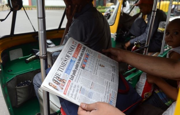 A commuter in an auto-rickshaw holds up a copy of an English-language Indian newspaper, with the headlines on exit polls  Exit poll results are dominating headlines in India. Photo: BBC