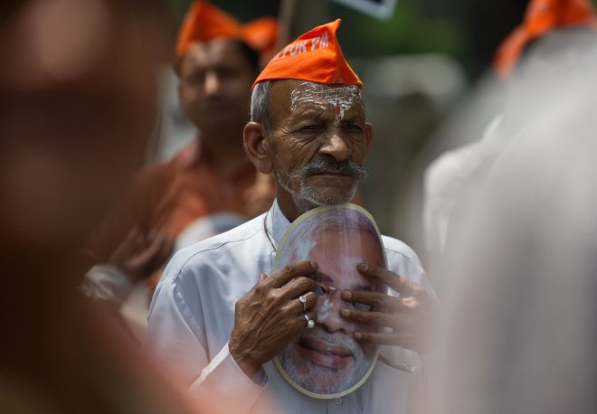 A BJP supporter listens to a speech during a protest against the Election Commission (EC) in New Delhi, yesterday. BJP workers protested against the denial of permission for BJP prime ministerial candidate Narendra Modi to hold a rally at a venue of his choice in Varanasi and requested the EC to remove the Electoral Officer of Varanasi.  Photo: AFP