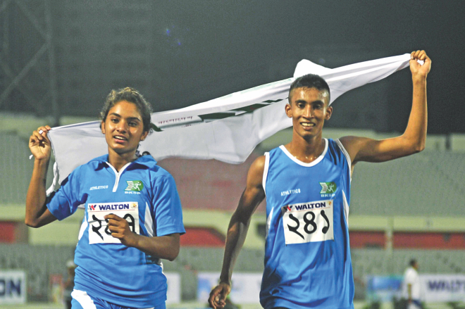 Disha Sultana (L) and Ashrafuzzaman of BKSP celebrate after becoming the fastest girl and boy in the Walton 30th National Junior Athletics Championships at the Bangabandhu National Stadium yesterday. PHOTO: STAR