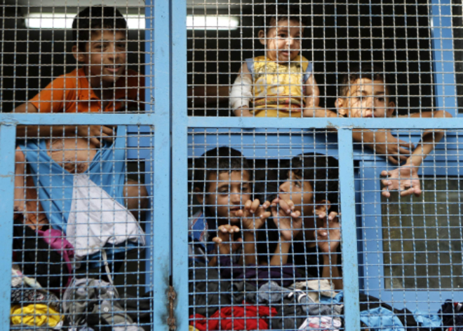 Displaced Palestinian children from Beit Hanun in the northern Gaza Strip stand behind the window of a classroom yesterday at a UN school in the refugee camp of Jabalia where families have taken refuge after fleeing heavy fighting in the Gaza Strip.  Photo: AFP