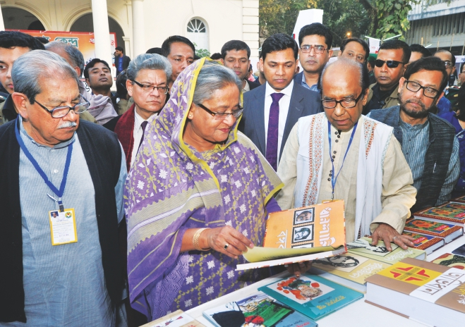 Prime Minister Sheikh Hasina flips the pages of a book at a stall in Ekushey Boi Mela in the capital yesterday right after the inaugurating the month-long book fair at Bangla Academy compound.  Photo: BSS