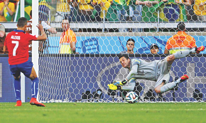 Brazil goalkeeper Julio Cesar saves a spot-kick from Chile forward Alexis Sanchez during the penalty shootout of the World Cup round of 16 match at the Mineirao Stadium in Belo Horizonte yesterday. Brazil won 3-2 on penalties. PHOTO: REUTERS