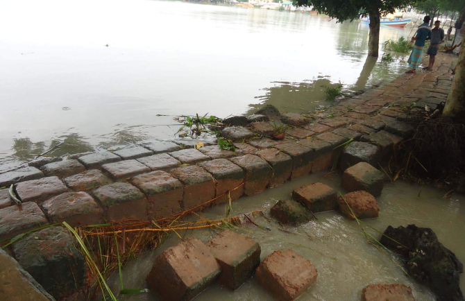 Patuakhali town was flooded again as tidal water entered it through breaches at different points of the dyke yesterday. Photo shows water overflowing the embankment in Katpatty area. PHOTO: STAR
