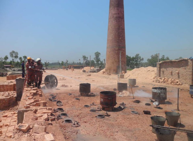 Fire Service men douse the fire of this illegal brick kiln in Badarganj upazila under Rangpur district yesterday as the High Court ordered its closure.  PHOTO: STAR