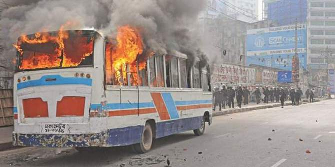 A minibus is set ablaze near Dainik Bangla intersection in Dhaka on February 13, 2013 during a clash between Jamaat-Shibir activists and law enforcers. Photo: STAR