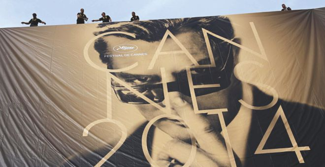 Workers set up a giant official poster of the 67th Cannes film festival. Photo Courtesy: Getty Images