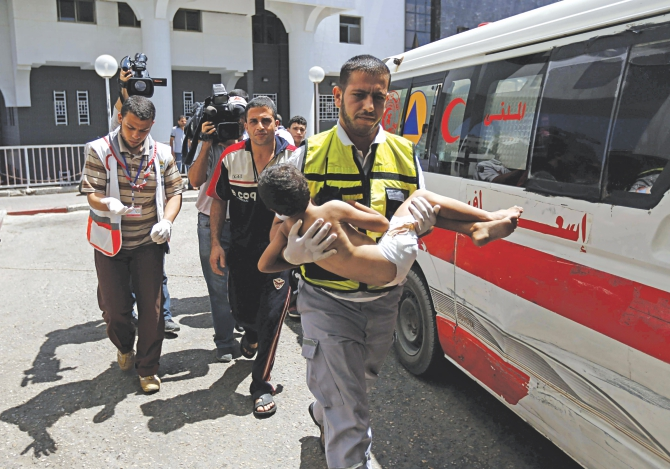 An emergency worker carries a child, wounded in an Israeli air strike on the Sheikh Radwan neighbourhood in Gaza, at the city's Al-Shifa hospital yesterday. Israeli warplanes struck targets across Gaza in retaliation to rocket fire after a 72-hour truce expired. Photo: AFP