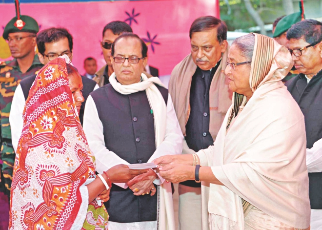 Prime Minister Sheikh Hasina hands over a cheque to a victim of the atrocities carried out on the Hindus at Malopara of Abhaynagar in Jessore right after the January 5 polls. The PM went to visit the area yesterday. Photo: PID